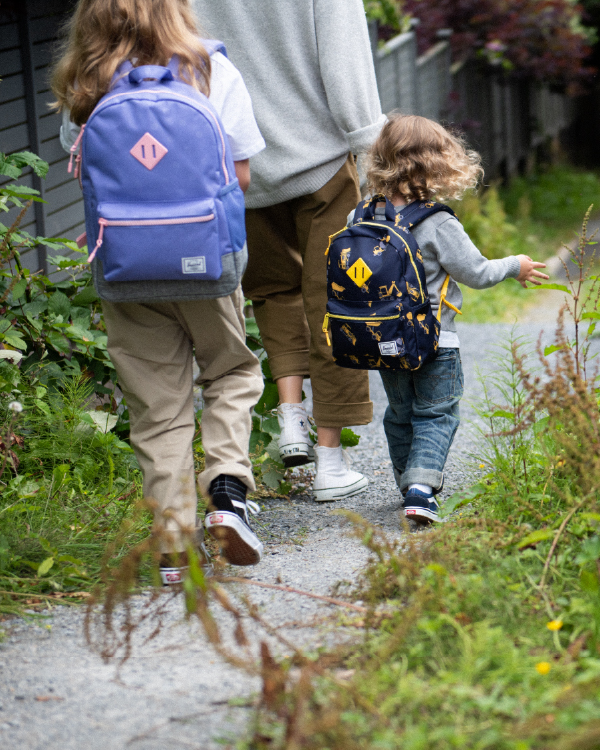 A couple of children walking down a trail with their mother.